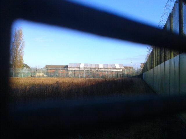 A tarpaulin covers the fire-damaged roof of 'Blue Block' at Campsfield - Photo by Corporate Watch 30.11.13