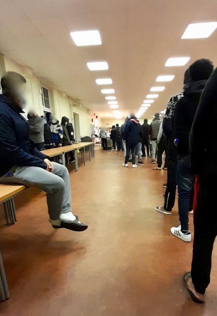 Image shows men in a queue close together with no social distancing