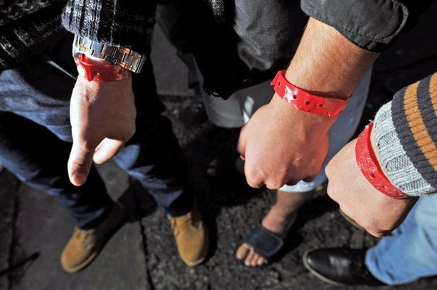 Image shows three people wearing red wrist bands